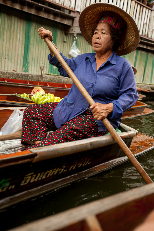 a travel photo of a woman in a hat in the floating market in bangkok thailand