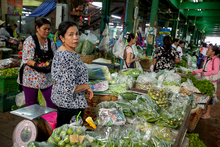 a travel photo of a woman at the flower market in bangkok thailand