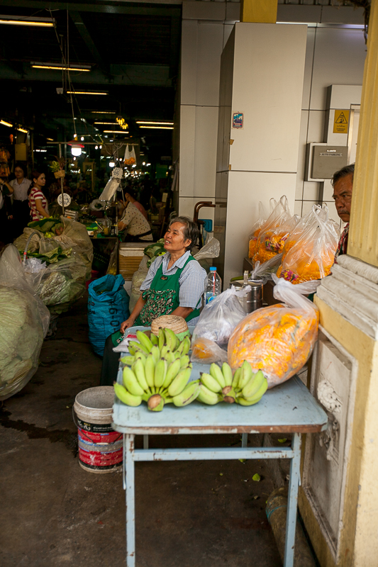a travel photo of a man looking at the flower market in bangkok thailand