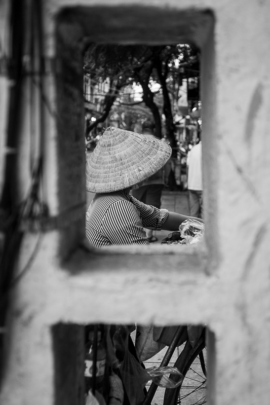 a travel photo of a woman in a hat in front of a concrete block in hanoi vietnam