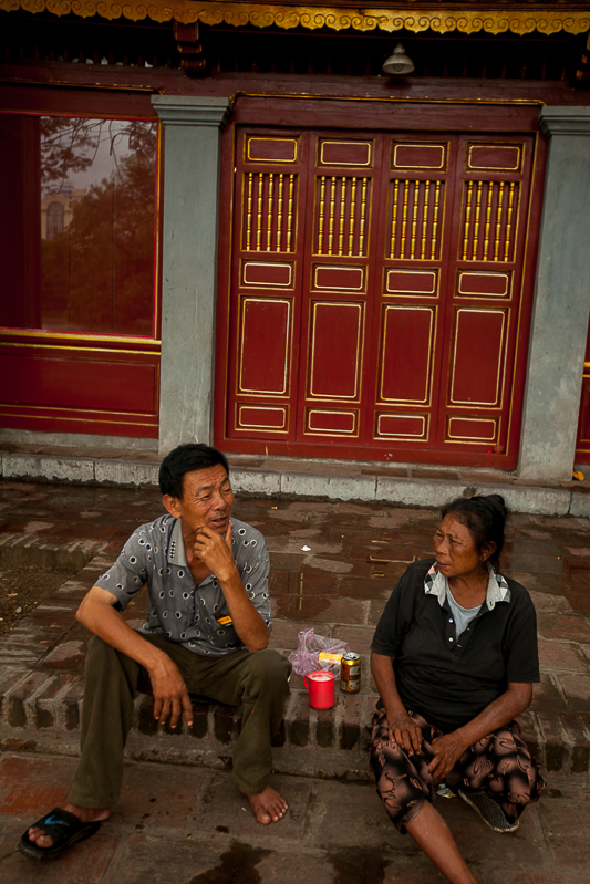 a travel photo of people talking in front of a temple in hanoi vietnam