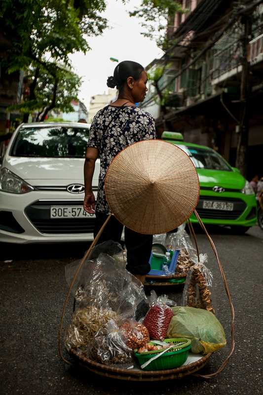 a travel photo of a woman vendor in hanoi vietnam