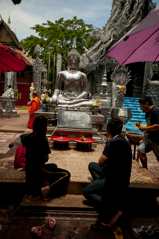 a travel photo of the silver temple with people praying in chaing mai thailand