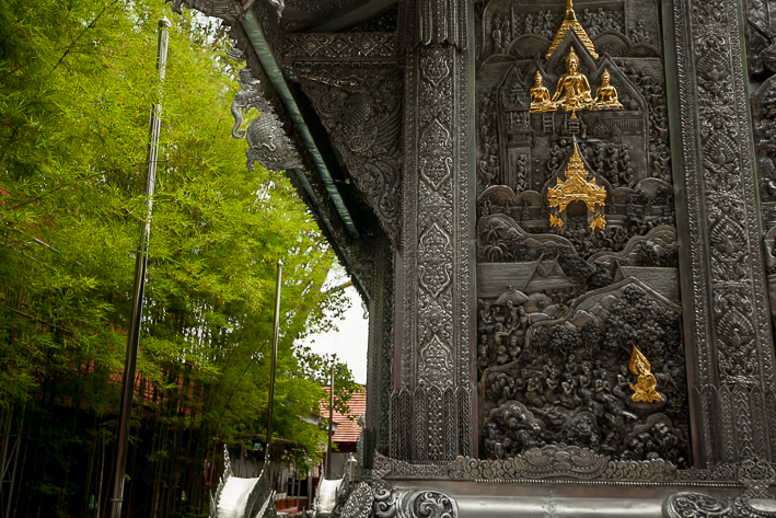 a travel photo of the silver temple beside trees in chaing mai thailand
