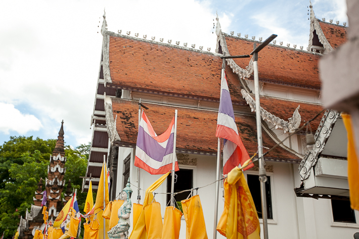 a travel photo of a temple with orange flags in chaing mai thailand