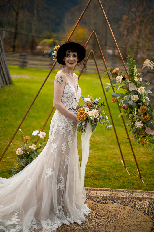 a styled wedding of a bride with a black hat and metal arbour in pemberton british columbia