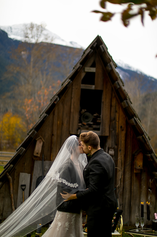 a styled wedding of a couple kissing with the veil being lifted in the autumn pemberton british columbia