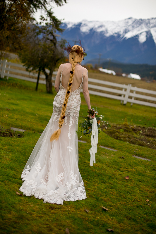 a styled wedding of the bride walking back of the dress with a long braid with roses in pemberton british columbia