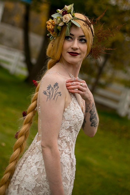 a styled wedding of the bride with tattoos and her hand up with a floral crown in autumn pemberton british columbia