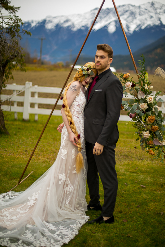 a styled wedding of the couple cuddling over a metal arbour with mountains in autumn pemberton british columbia