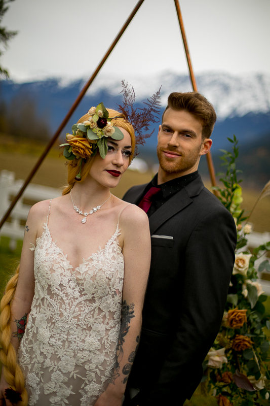a styled wedding of the couple over a metal arbour with flowers and mountains in autumn pemberton british columbia