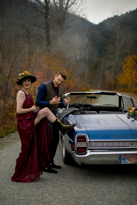 a styled wedding of the couple being silly in a burnaby sequinned dress beside a vintage car in autumn pemberton british columbia