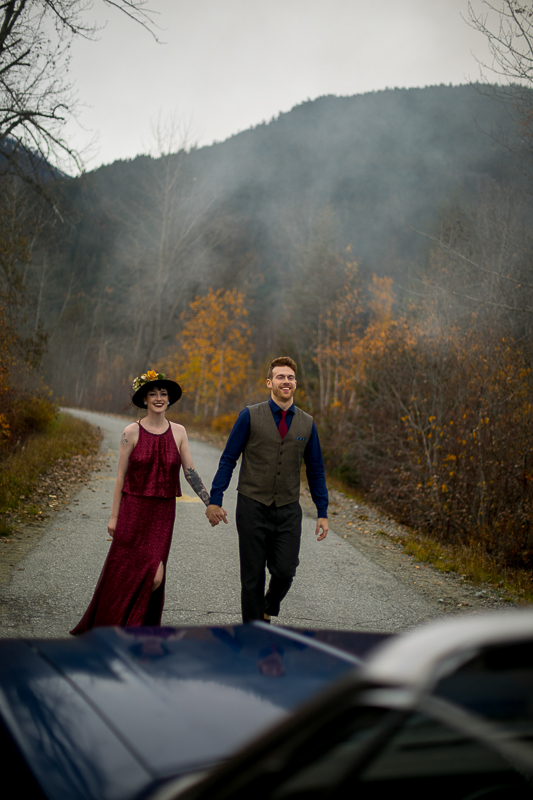 a styled wedding of the couple walking in a burnaby sequinned dress beside a vintage car in autumn pemberton british columbia