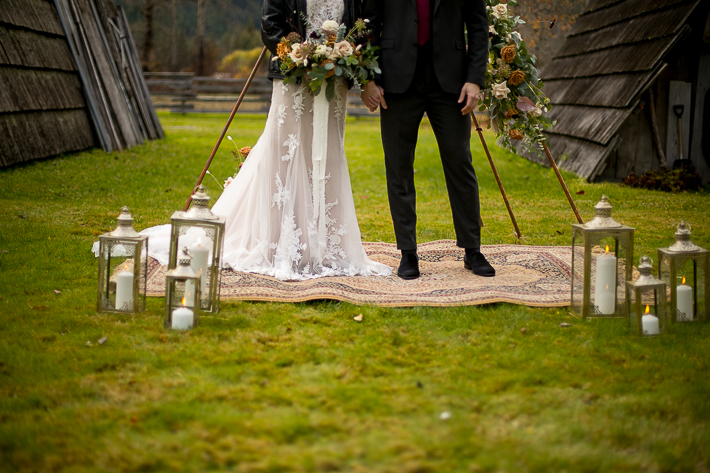 a styled wedding of the couple holding hands over a metal arbour with white candles and a moroccan carpet in pemberton british columbia