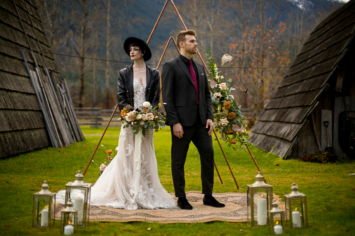 a styled wedding of the couple over a metal arbour with flowers and white candles in pemberton british columbia