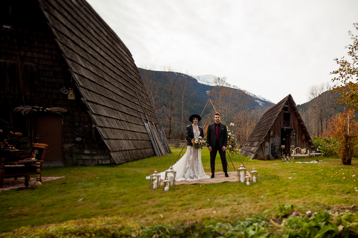 a styled wedding of the couple over a metal arbour with flowers in autumn pemberton british columbia