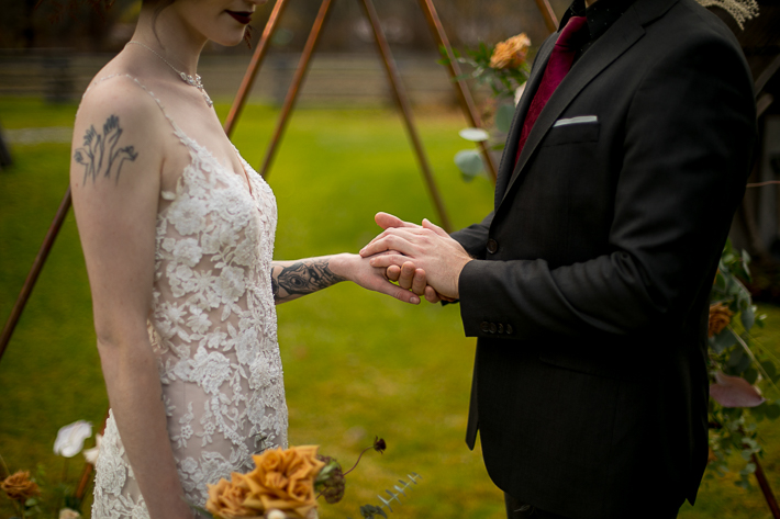 a styled wedding of the couple holding hands over a metal arbour with flowers in autumn pemberton british columbia