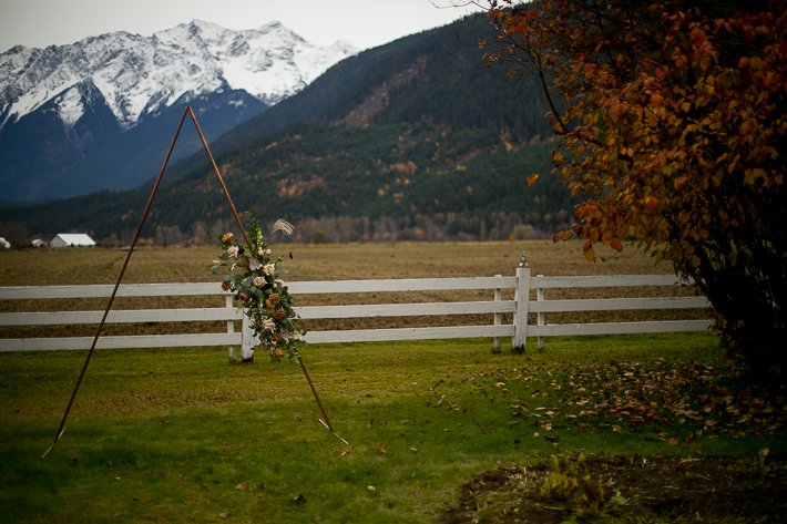 a styled wedding with the pointed metal arbour with flowers with mountains in autumn pemberton british columbia