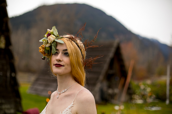 a styled wedding of the bride with a floral crown with wood buildings and mountains in autumn pemberton british columbia