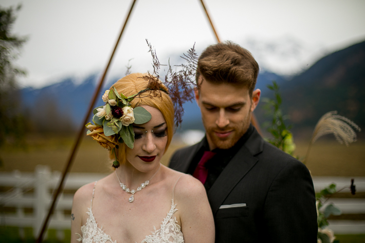 a styled wedding of the couple looking down over a metal arbour with flowers and mountains in autumn pemberton british columbia