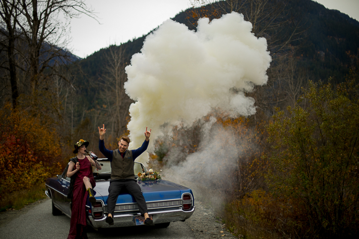 a styled wedding of the couple in a burnaby sequinned dress beside a vintage car with smoke bombs in autumn pemberton british columbia