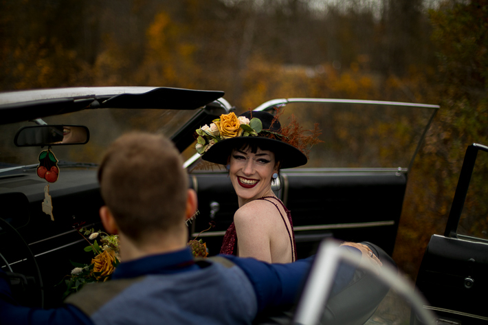 a styled wedding of the bride in a black flowered hat and burnaby sequinned dress in a vintage car in autumn pemberton british columbia