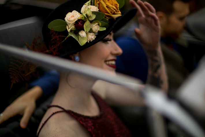 a styled wedding of the bride in a black flowered hat and burnaby sequinned dress through the window of a vintage car in autumn pemberton british columbia