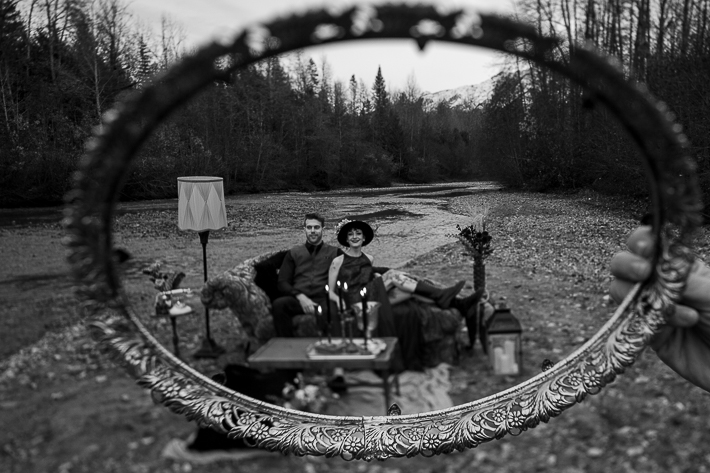 a styled wedding of a couple sitting with a frame around them on the rocky beach in autumn pemberton british columbia