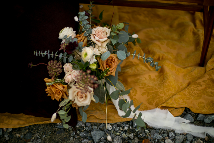 a styled wedding of setup of the bouquet on the rocky beach in autumn pemberton british columbia