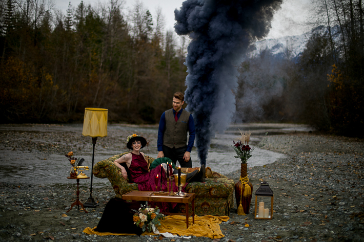 a styled wedding of a couple sitting with smoke bombs on the rocky beach in autumn pemberton british columbia
