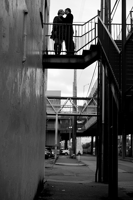 a fall engagement photo of a couple kissing in a fire escape in new westminster british columbia