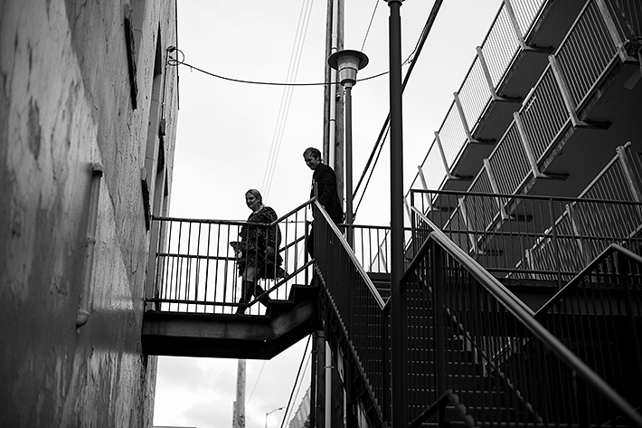 a fall engagement photo of a couple in a fire escape red wall in new westminster british columbia