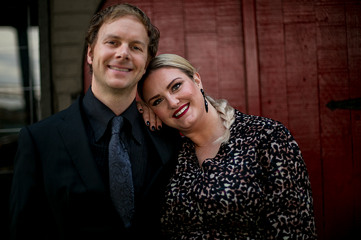 a fall engagement photo of a happy couple against red wall in new westminster british columbia