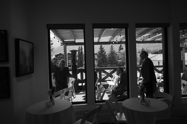 a summer wedding candids through the window of the ceremony in the hive gallery canmore alberta