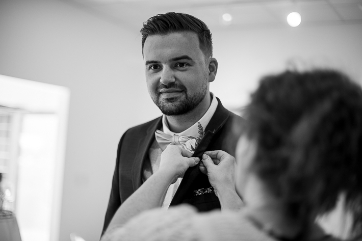 a summer wedding of the groom getting his boutonniere on before the ceremony in the hive gallery canmore alberta