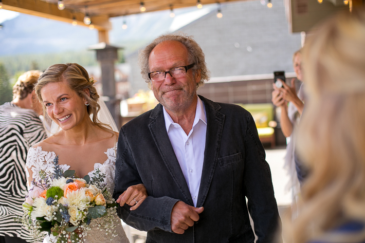 a summer wedding of the bride crying with her happy dad at the ceremony in the hive gallery canmore alberta