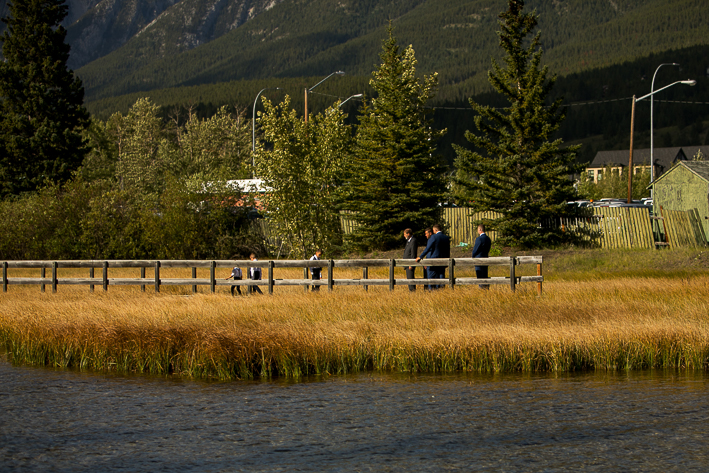 a summer wedding party photo on the policeman's boardwalk walking with mountains canmore alberta