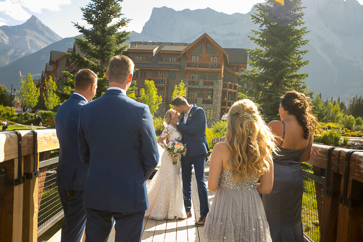 a summer wedding party photo on the policeman's boardwalk with mountains canmore alberta