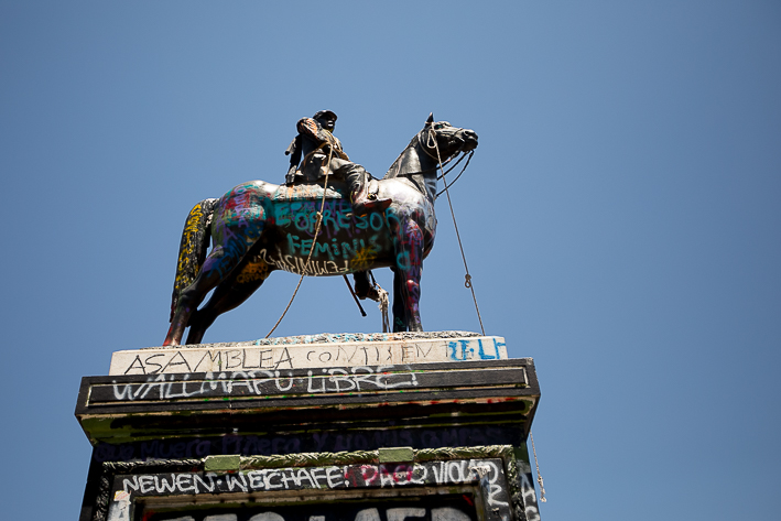a travel photo of the downtown square of a horse statue during the wage protests in santiago, chile, south america