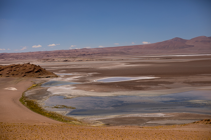 a travel photo of the atacama desert with blue, green, purple swirly salt flats, chile south america