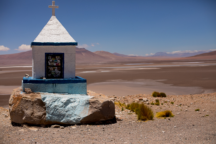 a travel photo of a roadside church in atacama desert with blue, green, purple swirly salt flats, chile south america