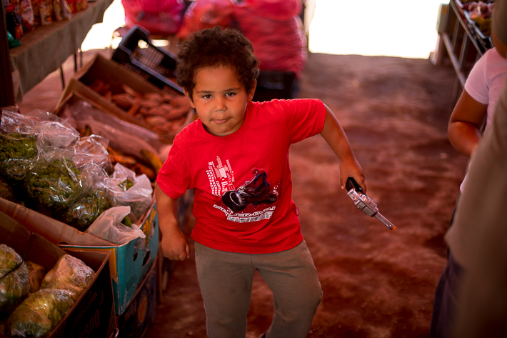 a travel photo of a fruit market with a child dancing in san pedro chile south america