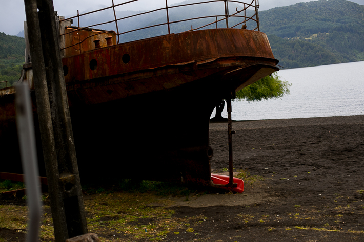 a travel photo of a rusty ship on a dark sand beach huilo huilo biological reserve chile south america