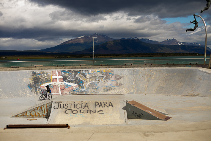 a travel photo of a man biking with a view of torres del paine in puerto natales chile south america