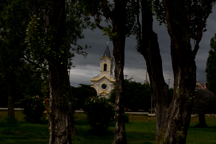 a travel photo of a church through trees in puerto natales chile south america