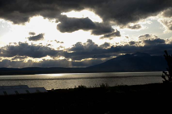 a travel photo of the sun peaking through the clouds with a bird of a view of torres del paine in puerto natales chile south america