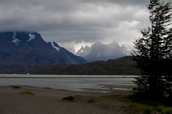 a travel photo of a beach with turquoise water with a mountain in los glaciares national park in torres del paine chile south america